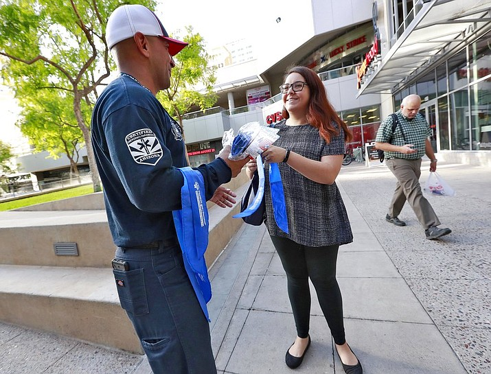 Phoenix firefighter Juan Rodriguez hands out a cooling neckerchief to morning commuter Arielle Thomas early Monday, July 23, 2018, in downtown Phoenix. Parts of Arizona and the Southwest are bracing for the hottest weather of the year with highs this week expected to approach 120 degrees. (AP Photo/Matt York)
