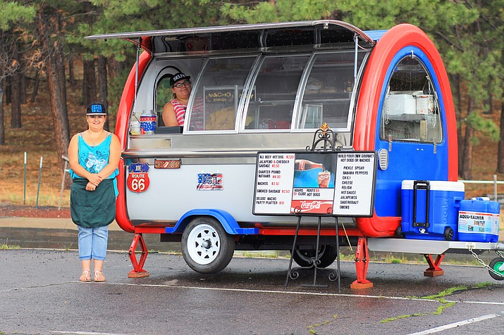 Carol DiFiore and Kendra Reed wait out the rain at Joe's Route 66 Hot Dogs in Williams.
