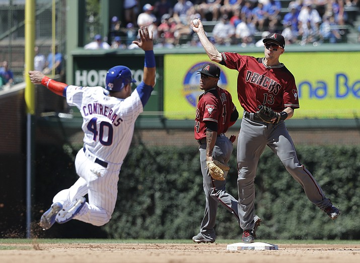 Arizona Diamondbacks' Nick Ahmed, right, turns a double play after forcing out Chicago Cubs' Willson Contreras at second base during the fourth inning of a baseball game Wednesday, July 25, 2018, in Chicago. The Cubs' Addison Russell was out at first. (Charles Rex Arbogast/AP Photo)