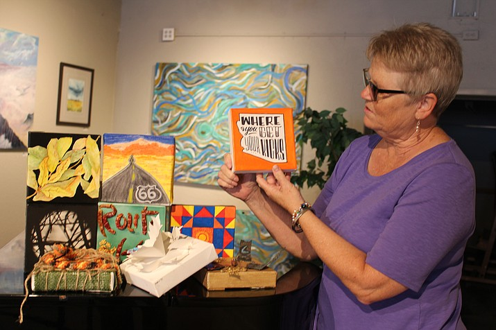 Pat Evans, volunteer manager of Kingman Center for the Arts studio and gallery, shows some of the canvas artwork that will be displayed and sold during KCA's 6x6 on Route 66 fundraiser art show. (Photo by Hubble Ray Smith/Daily Miner)