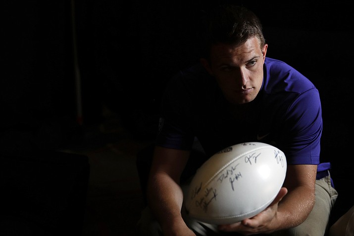 Washington quarterback Jake Browning hands the ball to head coach Chris Petersen, not pictured, in a holding room at the Pac-12 Conference NCAA college football media day in Los Angeles, Wednesday, July 25, 2018. (Jae C. Hong/AP)