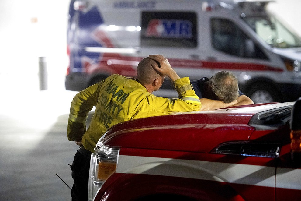 Marin County firefighters wait outside the Mercy Medical Center emergency room as an injured crew member receives treatment on Thursday, July 26, 2018, in Redding, Calif. Fueled by high temperatures and wind, the Carr Fire exploded Thursday leveling dozens of homes, burning three firefighters and killing a bulldozer operator. (AP Photo/Noah Berger)