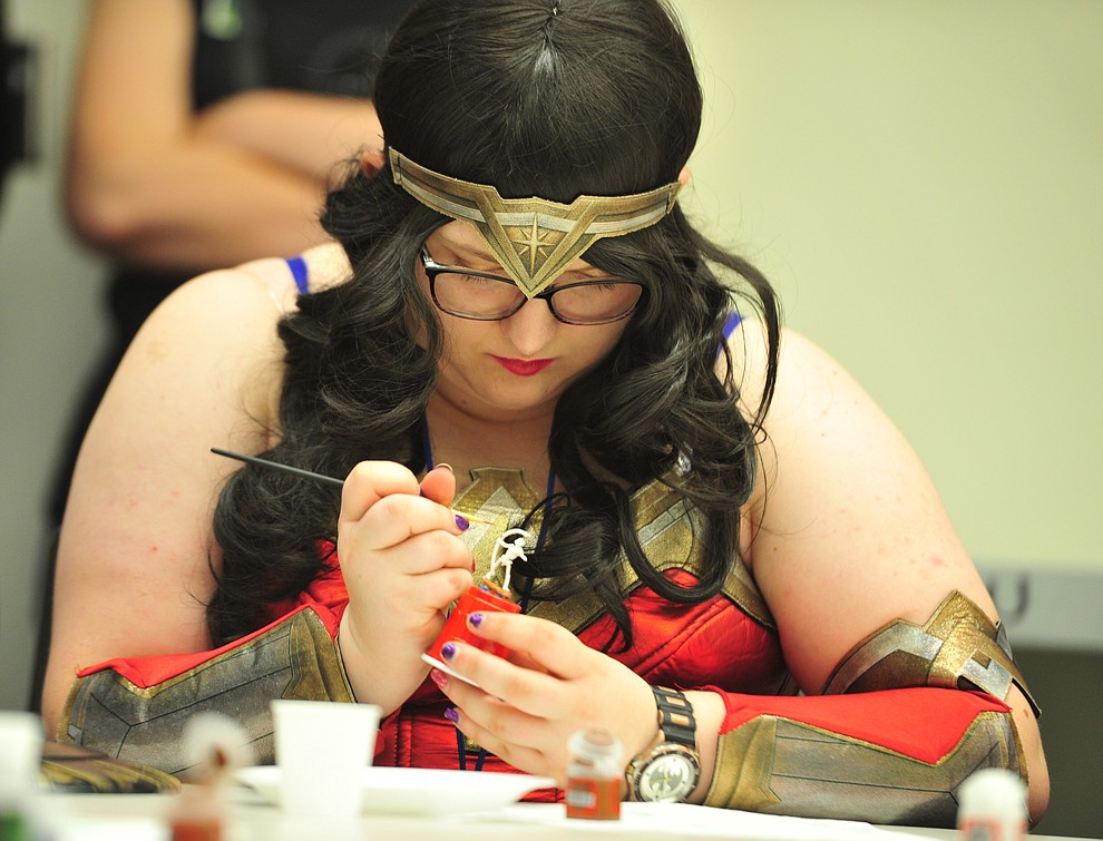 Wonderwoman aka Jesse Chisholm paints a minature at the Fandomania Comic Con event Saturday, July 28, 2018 in and around the Prescott Valley Library. (Les Stukenberg/Courier)