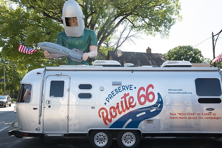 The Silver Bullet Airstream travel trailer being used as a media center by the National Trust for Historic Preservation's Route 66 road crew is parked under Gemini Giant in Wilmington, Illinois, one of many peculiar landmarks along the highway. (Photo by David Kafer/National Trust for Historic Preservation)