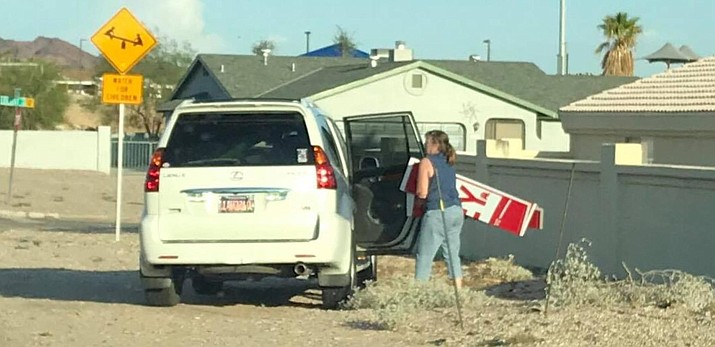 A woman who State Rep. Paul Mosley identified as Lake Havasu City business owner Debi Ashton is accused of removing one of Mosley's signs on Wednesday. The photograph was provided to Mosley by an acquaintance. (Courtesy)