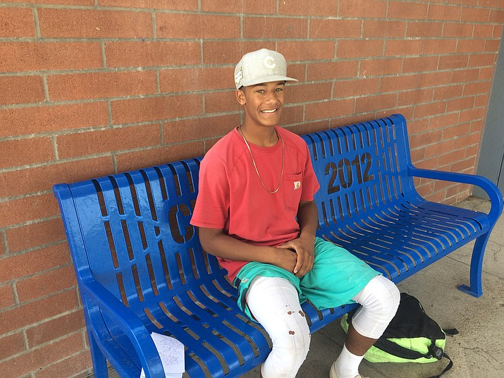 Malikija Hawkins sits on bench on the walkway entrance into Prescott High School after football practice on Friday, less than a week before the official start of school. (Nanci Hutson/Courier)