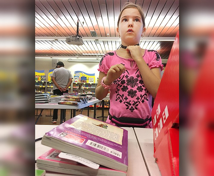 Kiena Jimenez, 9, celebrates the end of the Camp Verde library's Summer Reading Program by buying a few books. Kiena raised $225 for Heifer International's Schooling for Girls program. VVN/Bill Helm