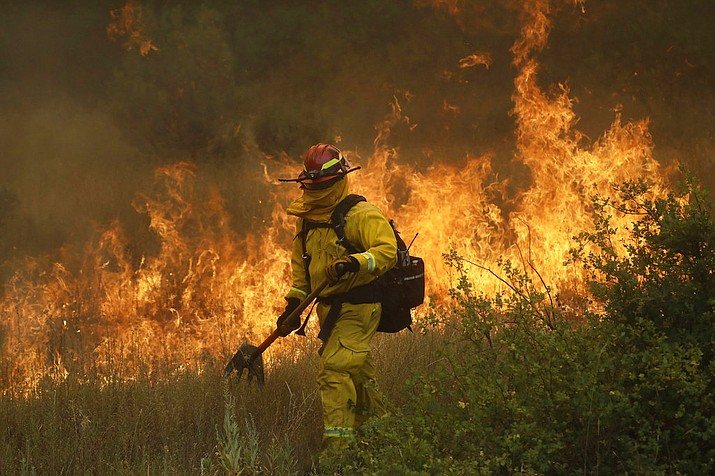 A firefighter with Cal Fire Mendocino Unit walks along a containment line as a wildfire advances Monday, July 30, 2018, in Lakeport, Calif. A pair of wildfires that prompted evacuation orders for thousands of people are barreling toward small lake towns in Northern California. (AP Photo/Marcio Jose Sanchez)