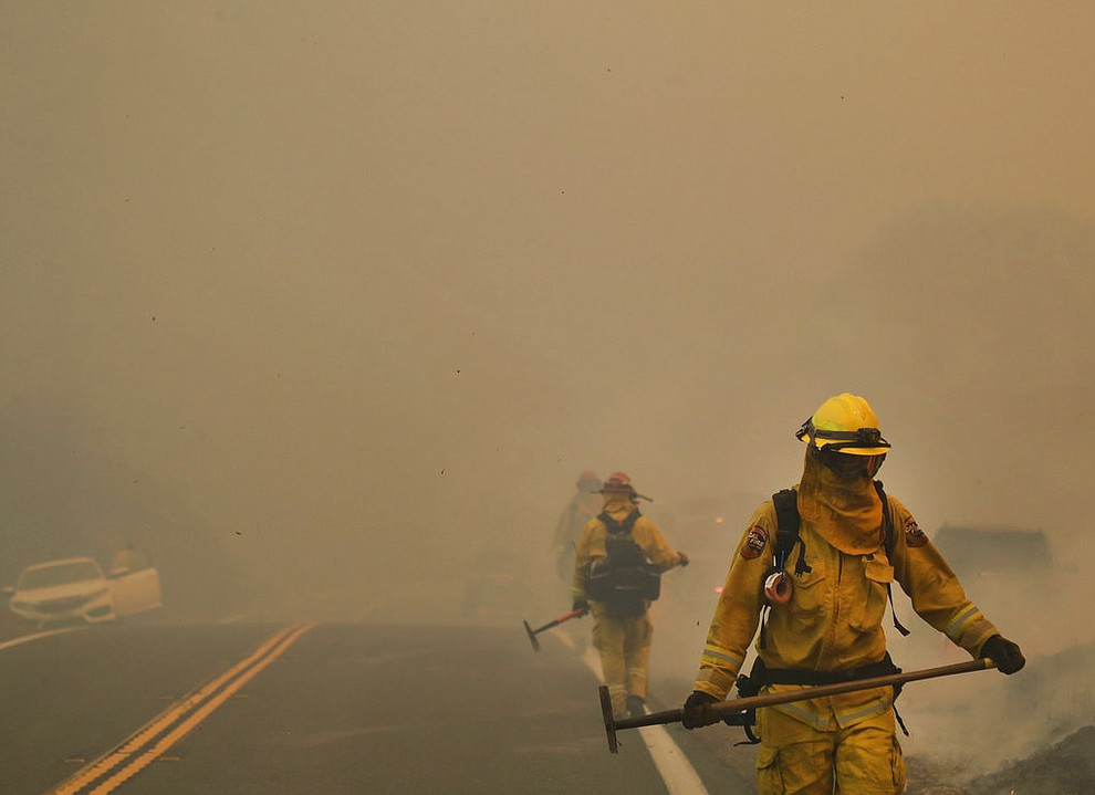 Smoke from an advancing wildfire covers a road as firefighters from Cal Fire Mendocino Unit work the fire lines Monday, July 30, 2018, in Lakeport, Calif. A pair of wildfires that prompted evacuation orders for thousands of people are barreling toward small lake towns in Northern California. (AP Photo/Marcio Jose Sanchez)
