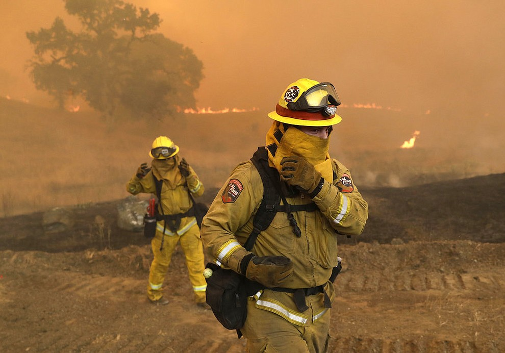 Firefighters with Cal Fire Mendocino Unit cover themselves from smoke and ash created by an advancing wildfire Monday, July 30, 2018, in Lakeport, Calif. A pair of wildfires that prompted evacuation orders for thousands of people are barreling toward small lake towns in Northern California.  (AP Photo/Marcio Jose Sanchez)