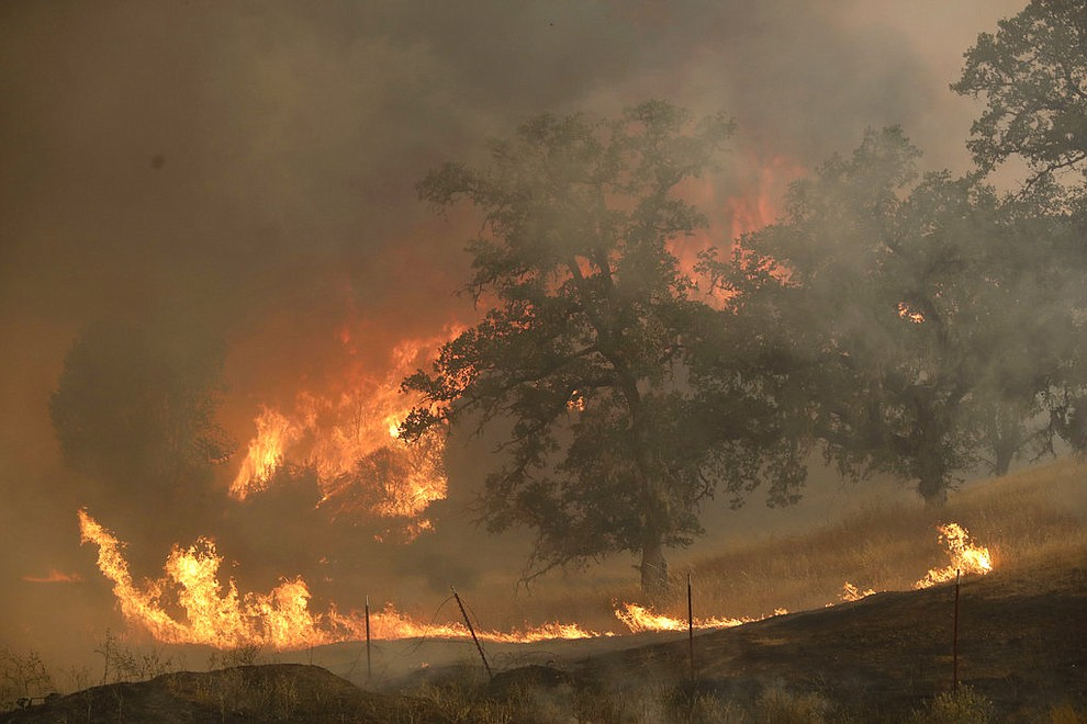 A wildfire lights up a hillside Monday, July 30, 2018, in Lakeport, Calif. A pair of wildfires that prompted evacuation orders for thousands of people are barreling toward small lake towns in Northern California. (AP Photo/Marcio Jose Sanchez)