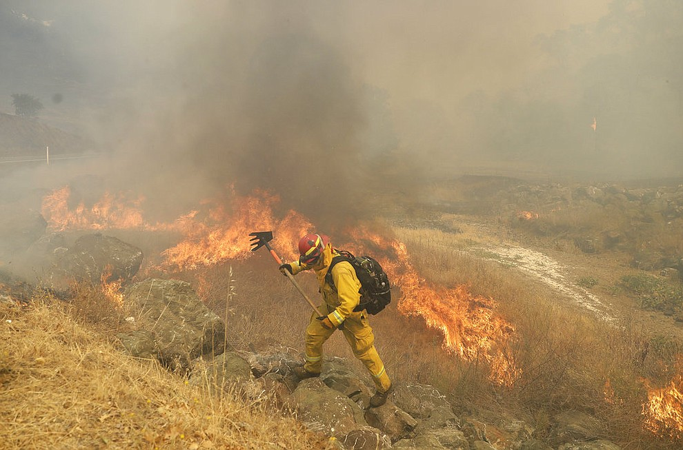 Don Jones, center, a firefighter with Cal Fire Mendocino Unit works with a rake as a wildfire reaches a road Monday, July 30, 2018, in Lakeport, Calif. A pair of wildfires that prompted evacuation orders for thousands of people are barreling toward small lake towns in Northern California. (AP Photo/Marcio Jose Sanchez)