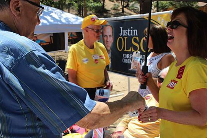 Joe Arpaio, left, exchanges campaign trinkets with Kelli Ward campaign volunteer Mardi Allen Benedict at the Mohave County Republican Picnic Saturday, July 28, 2018 at Hualapai Mountains County Park near Kingman. Shortly after this photo was taken, Arpaio says Ward approached them and grabbed his campaign sticker from Benedict's hand and threw it at him. (Courtesy photo/Joe Arpaio)