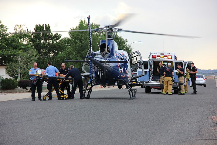 Emergency responders prepare to place an injured woman into a helicopter Monday evening, July 30, so she can be transported to a level-1 trauma center in Phoenix.