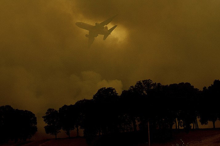 An air tanker passes behind a smoke plume while battling the River Fire in Lakeport, Calif., on Monday, July 30, 2018. A pair of wildfires that prompted evacuation orders for thousands of people are barreling toward small lake towns in Northern California. (AP Photo/Noah Berger)