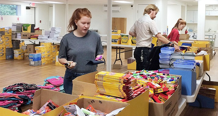 Bethleah Schaffer collects school supplies to fill backpacks for students in need July 27 at Trinity Lutheran Church. Her brother, Paul, center, and sister, Jennetta, also volunteered for this project, as well as siblings Jacob and Amanda, not pictured. (Sue Tone/Tribune)
