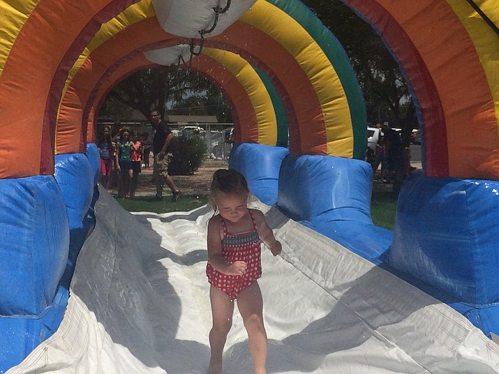 Sydnee Audis makes her way down a water inflatable at the Chino Valley Public Library's Summer Reading Program Finale at Memory Park Wednesday, July 25. (Jason Wheeler/Review)