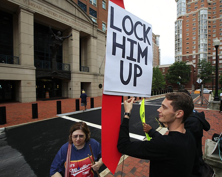 Protesters Gayelynn Taxey, left, and Danny Hastings, stand in front of the Alexandria Federal Court in Alexandria, Va., Tuesday, July 31, 2018, on day one of Paul Manafort's trial. (AP Photo/Manuel Balce Ceneta)
