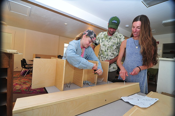 Student Gwen Felo, left, teacher Cal Seabaugh and teacher's aide Kristi Spreng assemble cubbies in the new middle school classroom at La Tierra Community School Tuesday, July 31, 2018. (Les Stukenberg/Courier)