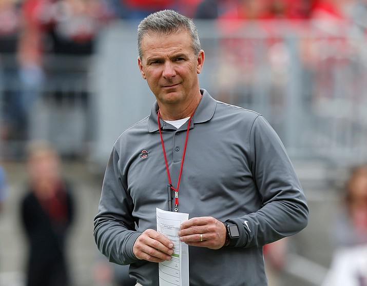 In this April 14, 2018, file photo, Ohio Setate coach Urban Meyer watches the NCAA college football team's spring game in Columbus, Ohio. Ohio State has placed Meyer on paid administrative leave while it investigates claims that his wife knew about allegations of abuse against an assistant coach years before he was fired last week. (Jay LaPrete/AP, file)