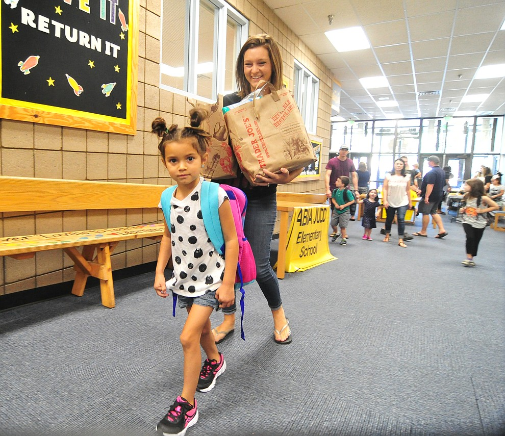 Kindergartener Rilyn Lucero walks in with Stephanie, with an armful of supplies, at Abia Judd Elementary School Thursday, August 2, 2018 as Prescott Unified School District starts the 2018-19 school year. (Les Stukenberg/Courier)
