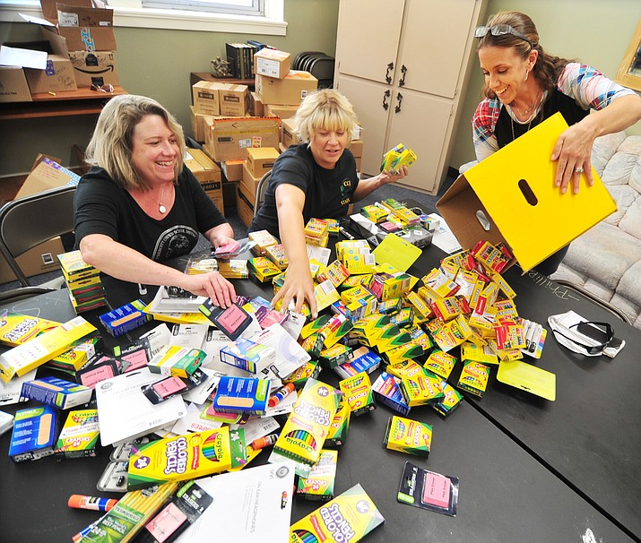 Prescott Unified Family Resource Center Coordinator Kelly Mattox and Coalition for Compassion and Justice (CCJ) Executive Director Jessi Hans and Lincoln Elementary School attendance clerk  Kerrie Wright sort donated Fair Start school supplies at Lincoln Friday, July 27, 2018. CCJ donated enough supplies so every child at Lincoln as well as two other schools only had a minimal list to buy for back to school. (Les Stukenberg/Courier)