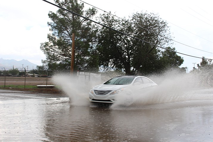 A car splashes water coming down Fairgrounds Boulevard during Thursday's monsoon thunderstorm. (Hubble Ray Smith/Daily Miner)