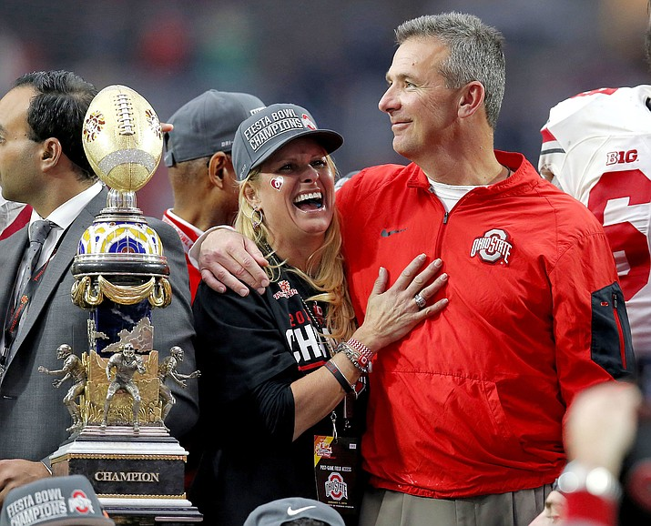 In this Jan. 1, 2016, file photo, Ohio State head coach Urban Meyer hugs his wife, Shelley, after their 44-28 win over Notre Dame in the Fiesta Bowl NCAA college football game, in Glendale, Ariz. Ohio State placed Meyer on paid administrative leave Wednesday, Aug. 1, 2018, while it investigates claims that his wife knew about allegations of abuse against former Buckeyes assistant Zach Smith, who was fired last week. (Rick Scuteri/AP, file)