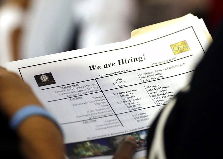 In this June 21, 2018 file photo, a job applicant looks at job listings for the Riverside Hotel at a job fair hosted by Job News South Florida, in Sunrise, Fla. Economists forecast that employers added 191,000 jobs in July, down from 213,000 in June but easily enough to lower the unemployment rate over time. The jobless rate is projected to decline to 3.9 percent, near an 18-year low, from 4 percent. The Labor Department's monthly jobs report will be released at 8:30 a.m. Eastern Friday, Aug. 3. (AP Photo/Lynne Sladky)