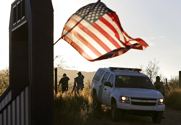 In this file photo, an American flag on a nearby resident's home waves in the breeze near a U.S. Border Patrol truck blocking the road leading to a search area near where Border Patrol Agent Brian Terry was killed northwest of Nogales, Ariz. (Greg Bryan/Arizona Daily Star via AP, 2010 File)