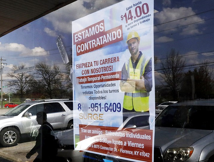 A poster announcing available jobs hangs in the window of the store La Guadalupana in Florence, Ky. One of President Donald Trump's top priorities — low unemployment — is complicating another: curbing immigration. The number of job openings is exceeding the number of Americans seeking jobs, leaving some employers looking beyond the border to fill openings. (AP Photo/Gregory Bull)