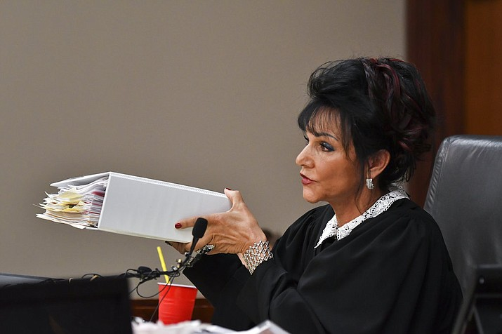 Ingham County Circuit Judge Rosemarie Aquilina holds up a binder of media requests that she says she has not responded to, Friday, Aug. 3, 2018, in Lansing, Mich. The Michigan judge who sentenced disgraced former sports doctor Larry Nassar to prison for molesting women and girls says she won't disqualify herself if higher courts send the case back to fix any errors. Aquilina on Friday defended her handling of the Nassar case. His appellate lawyers are accusing her of bias during a seven-day hearing in January when more than 150 victims spoke. At one point, the judge said Nassar deserved cruel punishment if the Constitution would allow it. (Matthew Dae Smith/Lansing State Journal via AP)