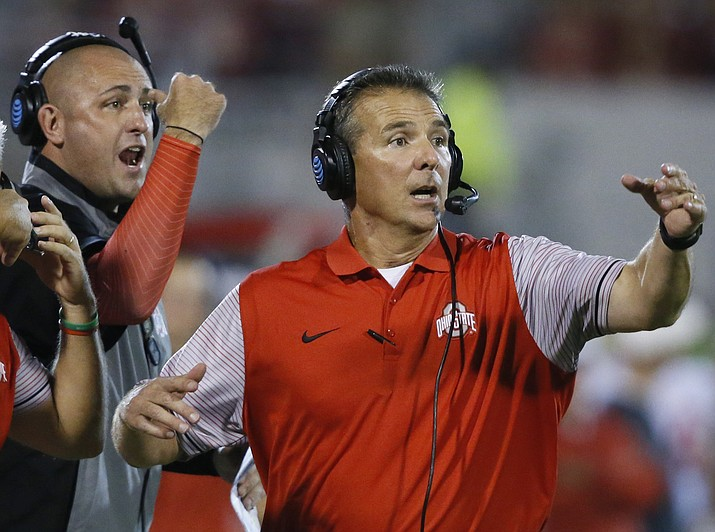 In this Sept. 17, 2016, file photo, Ohio State head coach Urban Meyer, right, and then-assistant coach Zach Smith, left, gesture from the sidelines during an NCAA college football game against Oklahoma in Norman, Okla. Ohio State expects to open fall camp as scheduled on Friday, Aug. 3, 2018, but without coach Urban Meyer.  Meyer was put on administrative leave on Wednesday, Aug. 1, over the handling of a longtime assistant who has been accused of domestic violence. Co-offensive coordinator Ryan Day will be running the team while Ohio State investigates claims that Meyer's wife knew about 2015 allegations of abuse against former Buckeyes assistant Zach Smith, who was fired last week. (Sue Ogrocki/AP, file)