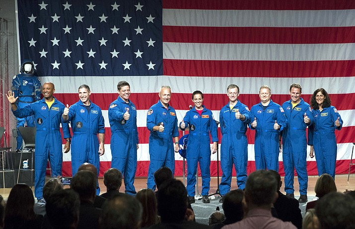 Astronauts, from left to right, Victor Glover, Michael Hopkins, Robert Behnken, Douglas Hurley, Nicole Mann, Christopher Ferguson, Eric Boe, Josh Cassada and Sunita Williams give a thumbs up to the crowd after NASA announced them as astronauts assigned to crew the first flight tests and missions of the Boeing CST-100 Starliner and SpaceX Crew Dragon, Friday, Aug. 3, 2018, in Houston. The astronauts will ride the first commercial capsules into orbit next year and return human launches to the U.S. (AP Photo/David J. Phillip)