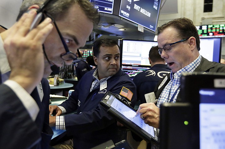 Specialist Dilip Patel, center, works with traders on the floor of the New York Stock Exchange, Friday, Aug. 3, 2018. U.S. stocks are mostly higher Friday morning after the Labor Department said hiring remained solid in July. (Richard Drew/AP)