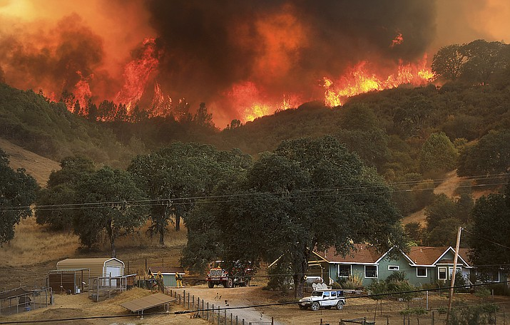 Flames from a wildfire advance down a hillside, towering over homes off Scotts Valley Road, Thursday, near Lakeport, Calif. (Kent Porter/The Press Democrat, via AP)