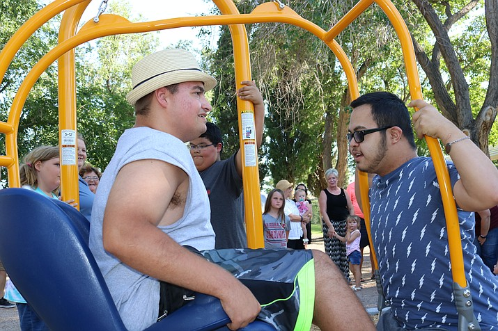 David (left) and Jessie from Kingman 66 Special Olympics were some of the first to try out Metcalfe Park's new Game Time Expression Swing at a ribbon cutting Friday. (Photo by Travis Rains/Daily Miner)