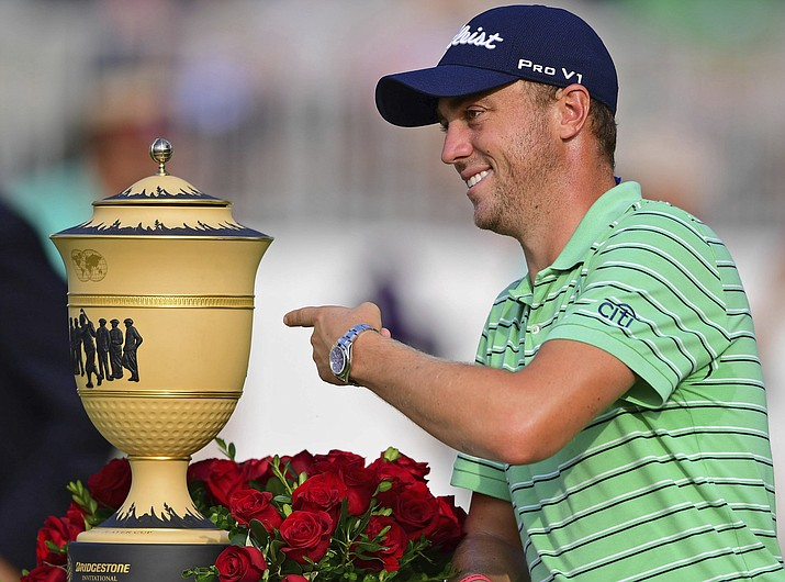 Justin Thomas points the Gary Player Cup trophy after winning the final round of the Bridgestone Invitational golf tournament at Firestone Country Club, Sunday, Aug. 5, 2018, in Akron, Ohio. (David Dermer/AP Photo)