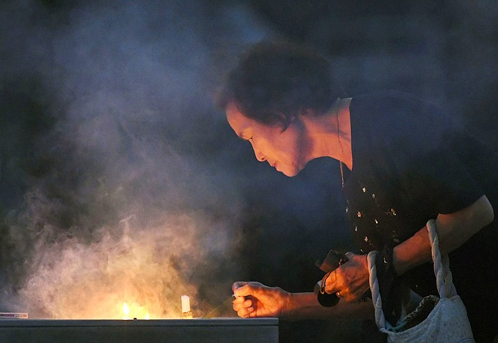 A woman burns a stick of incense at the cenotaph dedicated to the victims of atomic bombing at Hiroshima Peace Memorial Park in Hiroshima, western Japan, Monday, Aug. 6, 2018, marking the 73rd anniversary of the bombing. (Yohei Nishimura/Kyodo News via AP)