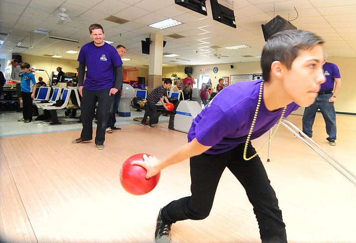 Jonathan Delker watches Dylan Chavez bowl as Bigs an Littles bowl during the kickoff for the Bowl for Kids Sake campaign at Antelope Lanes in Prescott Valley Saturday, Feb. 4, 2017. (Les Stukenberg/Courier)
