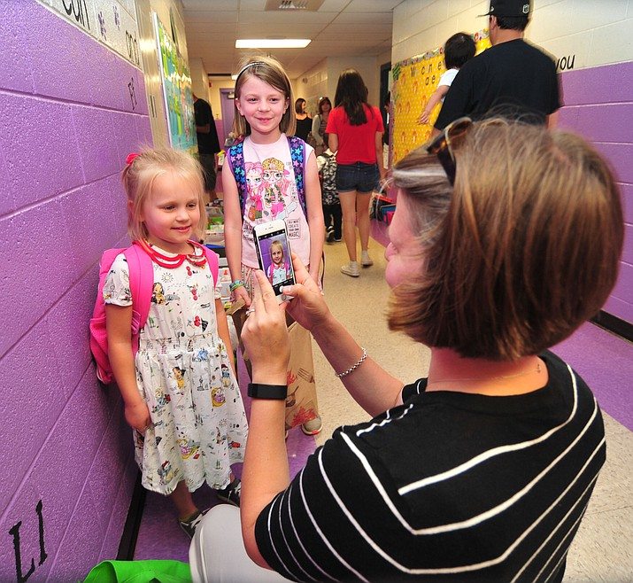 Beth Parknowitz gets photos of her daughters Kasey, left, and Emma during the first day of school at Coyote Springs Elementary in Prescott Valley Monday, Aug. 6, 2018.  (Les Stukenberg/Courier)
