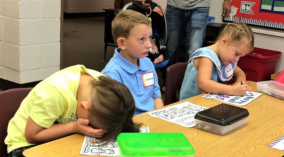 Some new kindergartners busied themselves with coloring, while others appear a little lost on the first day of school Monday, Aug. 6, at Mountain View Elementary School in Prescott Valley. From left are Erik Theodoroff, Jonathan Casteel and Maddy Parks. (Sue Tone/Courier)