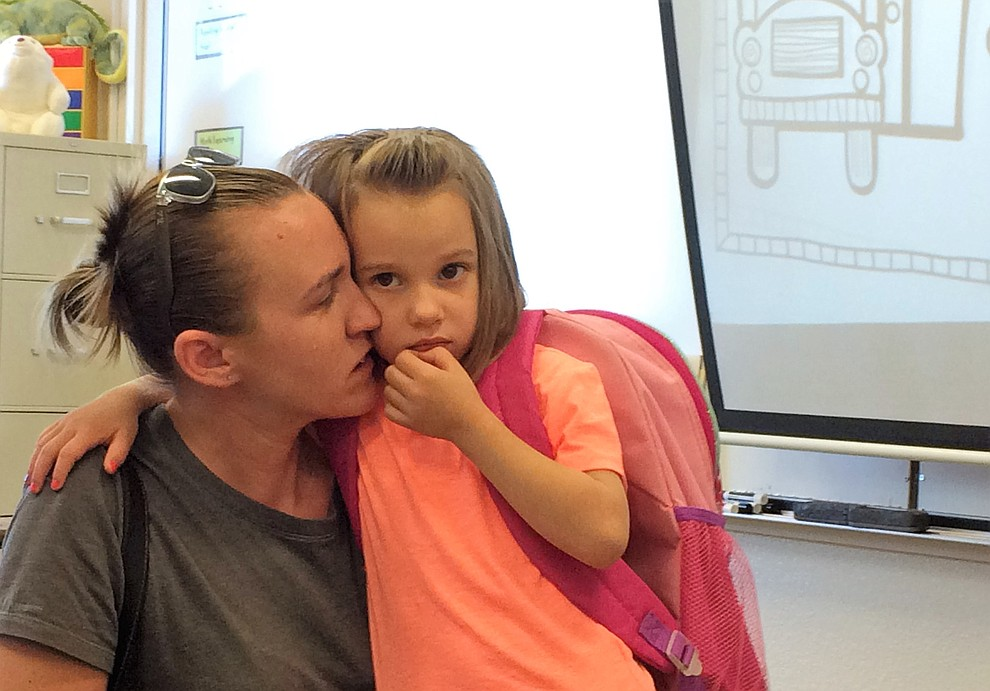 Looking a little apprehensive, new kindergarten student Kyra Boals is comforted by her mother, Jami Dowog, on the first day of school Monday, Aug. 6, at Mountain View Elementary School in Prescott Valley. (Sue Tone/Courier)
