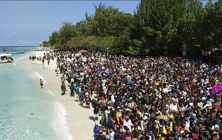 In this photo released by the Indonesian Marine Police, tourists affected by a strong earthquake line up on a beach as they wait to be evacuated on Gili Trawangan Island, Indonesia, Monday, Aug. 6, 2018. Indonesian authorities said Monday that rescuers still haven't reached some devastated parts of the tourist island of Lombok after a powerful earthquake flattened houses and toppled bridges, killing a number of people and shaking neighboring Bali. The death toll is expected to rise. (AKBP. Dewa Wijaya, West Nusa Tenggara Marine Police via AP)