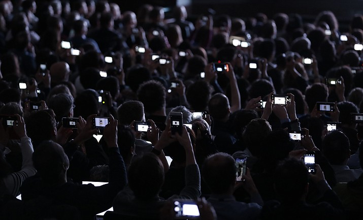 In this March 27, 2018 photo, people record the reveal of the new iPad during an Apple event at Lane Technical College Prep High School in Chicago. The Trump administration's hit list of Chinese products facing import taxes includes key components used in gadgets that can be wirelessly operated through a smartphone or another device. Apple's iPhones are assembled in China. (Charles Rex Arbogast/AP, File)