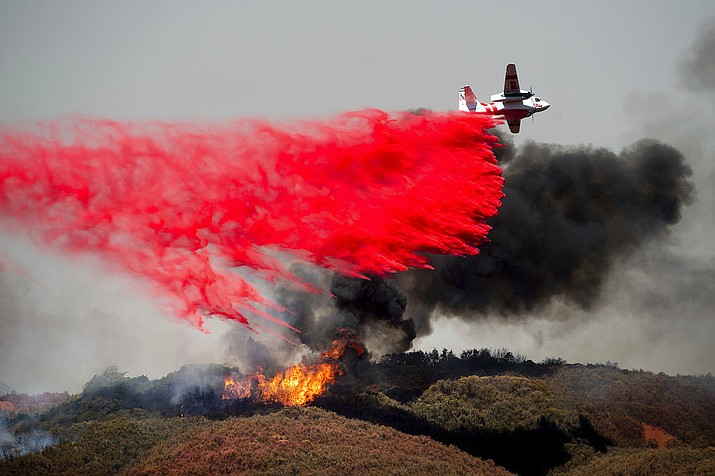 In this Monday, July 30, 2018, file photo, an air tanker drops retardant on a wildfire burning near Lakeport, Calif. Authorities say a rapidly expanding Northern California wildfire burning over an area the size of Los Angeles has become the state's largest blaze in recorded history. It's the second year in a row that California has recorded the state's largest wildfire. (AP Photo/Noah Berger, File)