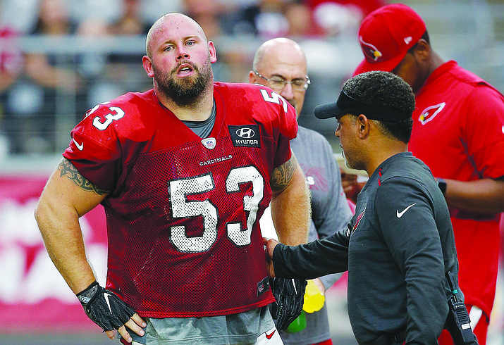 An injured Arizona Cardinals center A.Q. Shipley (53) is checked by head athletic trainer Tom Reed, right, as Shipley walks off the field during an NFL football practice Saturday, Aug. 4, 2018, in Glendale, Ariz. (Ross D. Franklin/AP Photo)