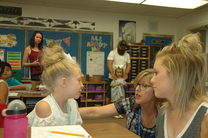 Del Rio Elementary School third grade teacher Robin Bond and Lacee Fletcher help Fletcher's daughter Emma Fletcher get settled for her first day of third grade. (Jason Wheeler/Review)