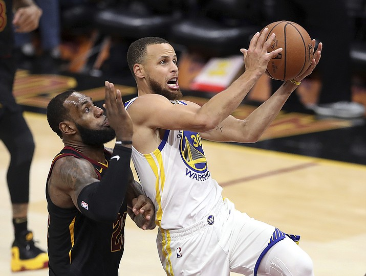 Golden State Warriors' Stephen Curry goes to the basket against Cleveland Cavaliers' LeBron James, left, during the second half of Game 3 of basketball's NBA Finals in Cleveland on June 6, 2018. Curry can only imagine the intensity level of the Lakers-Warriors rivalry now that LeBron James has landed in L.A. After four straight NBA Finals against James and the Cleveland Cavaliers, two-time defending champion Golden State will get four matchups against James during the regular season. (Carlos Osorio/AP Photo, file)