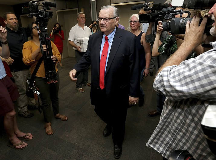 In this May 22, 2018 file photo, former Arizona Sheriff Joe Arpaio arrives at the Arizona Secretary of State's office in Phoenix, to turn in petition signatures in his bid to appear on the ballot in the race to succeed retiring U.S. Sen. Jeff Flake. County officials in metro Phoenix voted recently to ask the U.S. Supreme Court to review a ruling that concluded the county is liable for Arpaio's actions in cracking down on immigrants during traffic stops. The county's top prosecutor says the goal is to correct decisions that misapplied laws over which government agencies are the proper targets in lawsuits. (Matt York/AP, file)